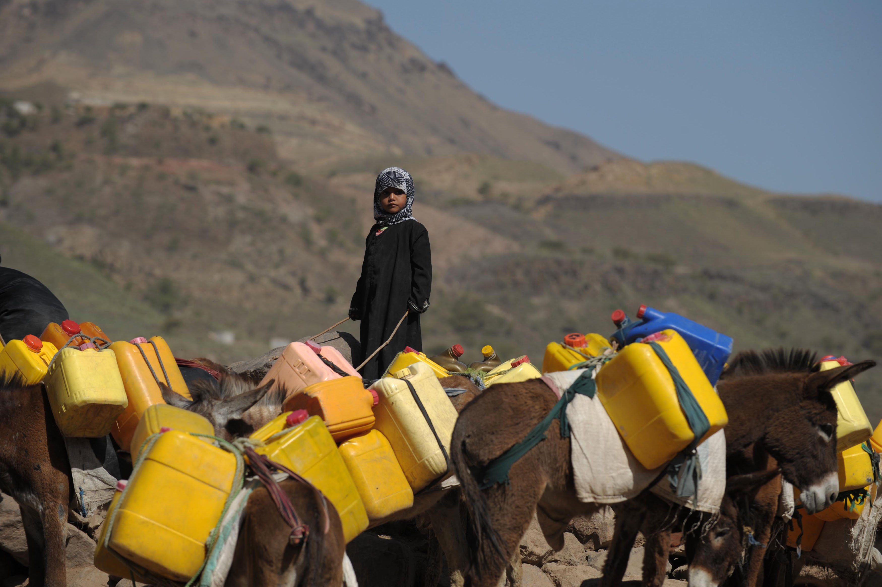 Dívka stojí vedle oslů a čeká na vodu v Bit al-Haidari, 200 kilometrů na jih od San'á