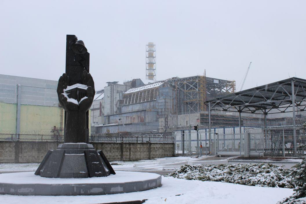 """Černobyl je plný pomníků. Tento z roku 2006 nesoucí nápis """"Těm, kdo zachránili svět"""" stojí hned před tzv. starým sarkofágem (budova v pozadí), pod nímž je pohřben havarovaný 4. blok"""