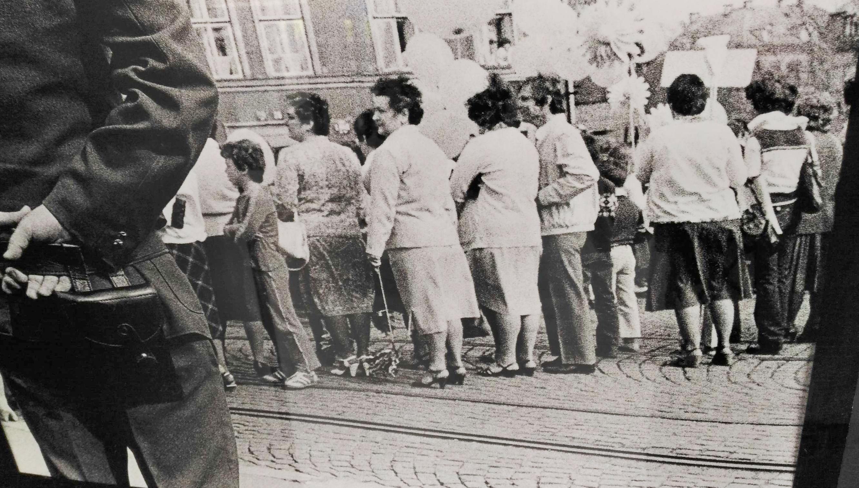 Příslušník veřejné bezpečnosti s revolverem kontrolující prvomájový průvod na fotce Petra Šimra