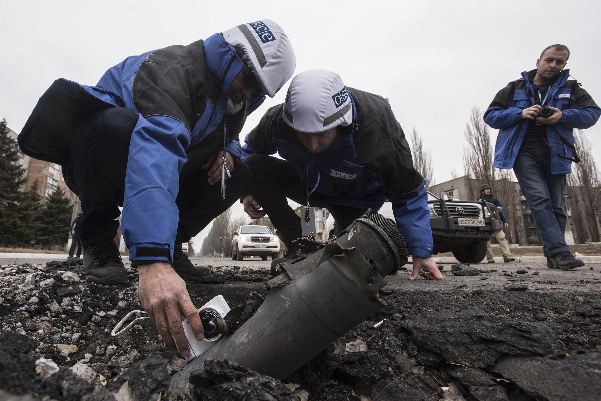 Inspektoři OBSE na východě Ukrajiny měří úhel dopadu dělostřeleckého granátu