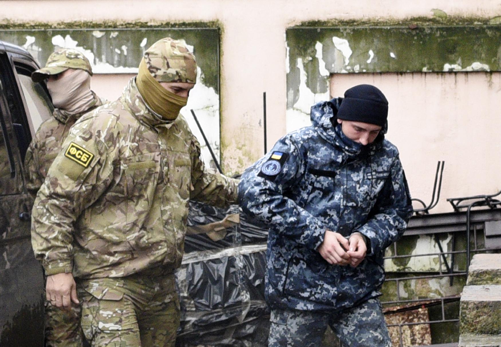 Ukrajinský námořník eskortovaný agentem FSB do soudní síně v Simferopolu