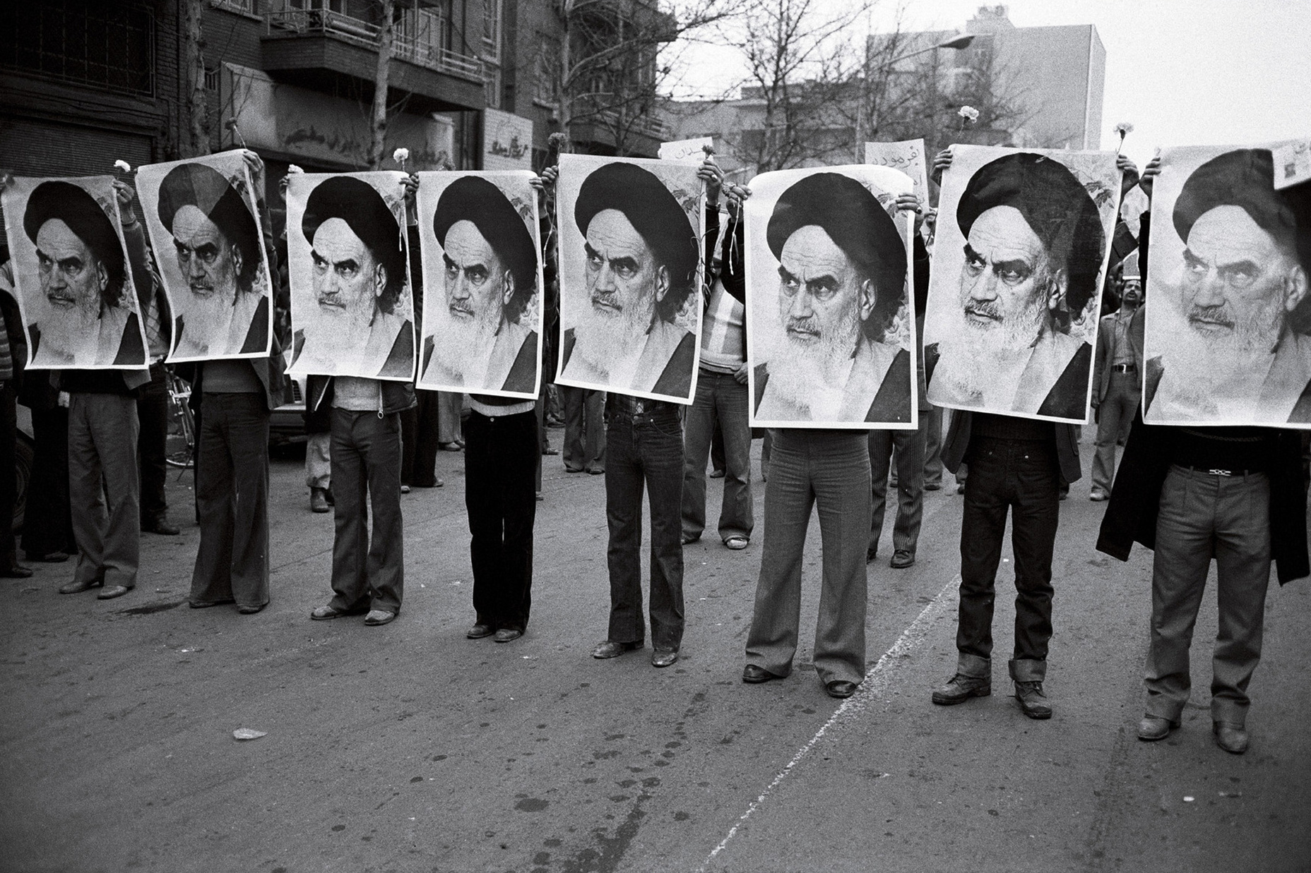 Íránská revoluce: řada mužů s obrázkem ajatolláha Chomejního (1978)