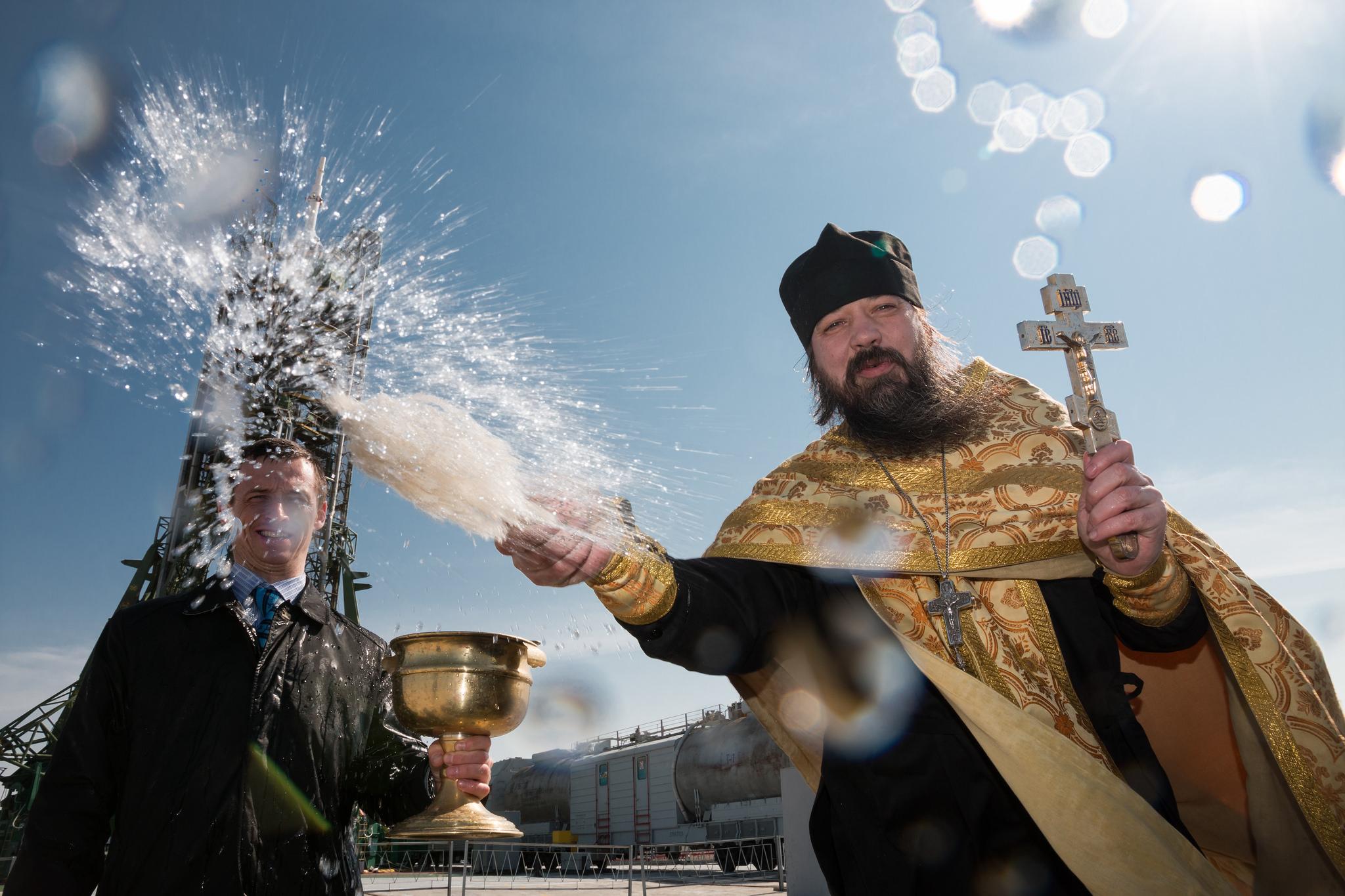Pravoslavný kněz žehná posádce kosmické lodi Sojuz na kosmodromu Bajkonur