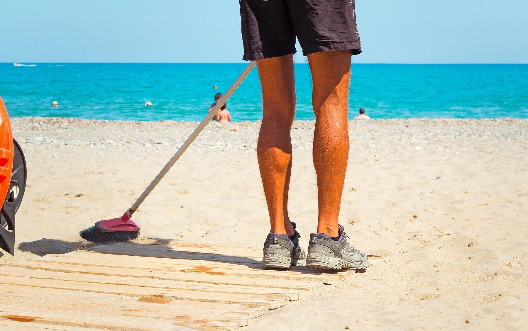 Pracovník uklízí na pláži