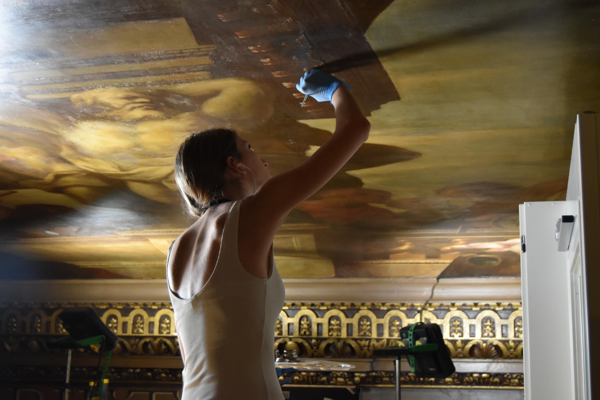 Restaurátoři barokní malbu jemně čistí, zacelují drobné prasklinky a fixují.