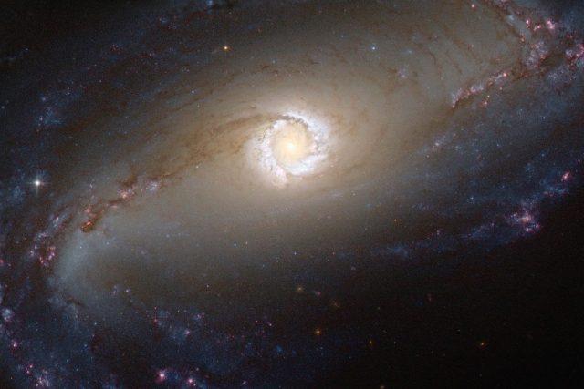 Galaxie NGC 1097 patří do skupiny Seyfertových galaxií. Aktivní černá díra v jejím středu požírá okolní disk a uvolňuje se tak intenzivní záření. | foto: NASA /ESA/HST