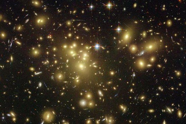 Temná hmota - masivní kupa žlutavých galaxií, zdánlivě chycená v červené a modré pavučině pokroucených galaxií v pozadí. Snímek z Hubbleova vesmírného teleskopu