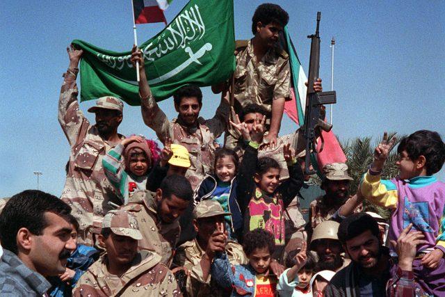 Civilisté a koaliční vojáci mávají vlajkami Kuvajtu a Saúdské Arábie na oslavu ústupu iráckých vojsk z Kuvajtu po operaci Pouštní bouře