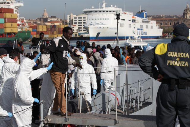 Migranti vystupují z lodi v sicilské Catanii