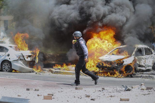 Hasič v jihoizraelském městě Aškelon kráčí vedle automobilů zasažených raketou vystřelenou z pásma Gazy