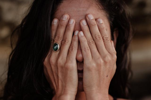 Žena s obličejem v dlaních