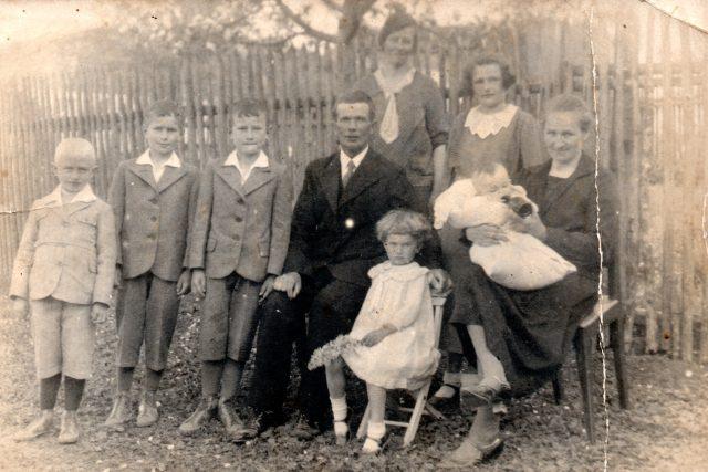 Rodinná fotografie z roku 1935,  Marie Henzlová sedí na židličce před svými rodiči | foto: Post Bellum