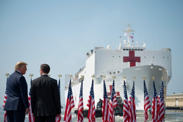 Pandemii covid-19 pomáhá v USA zvládnout i vojenská zdravotnická loď /US Defense Secretary Mark Esper (R) and US President Donald Trump watch as the hospital ship USNS Comfort departs Naval Base Norfolk/