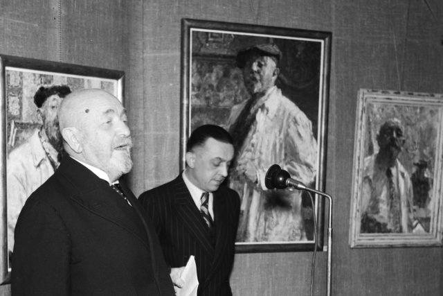 Malíř Ludvík Kuba (vlevo) na výstavě svých obrazů v salonu Výtvarné dílo v Praze. 15.4.1943