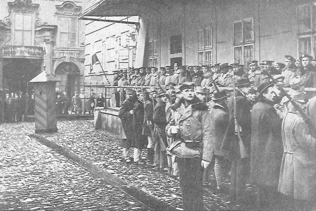 Setnina námořníků drží stráž před vojenským velitelstvím na konci října 1918 po vzniku Československa