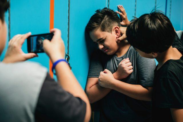 Spolužáci šikanují a nahrávají chlapce ve škole