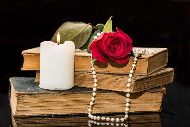 Knihy básní se svíčkou,  růží a perlami | foto: Pixabay