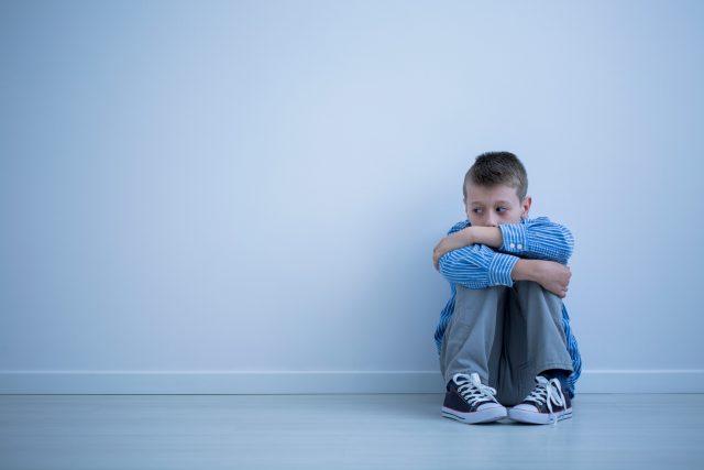 Smutný osamělý chlapec sedí sám v pokoji