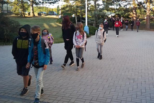 Žáci míří do školy v rouškách.