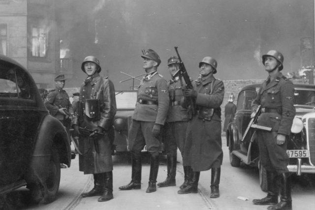 Generál SS Jürgen Stroop (druhý muž zleva s polní čepicí) a jeho muži pozorují hořící domy ve varšavském ghettu