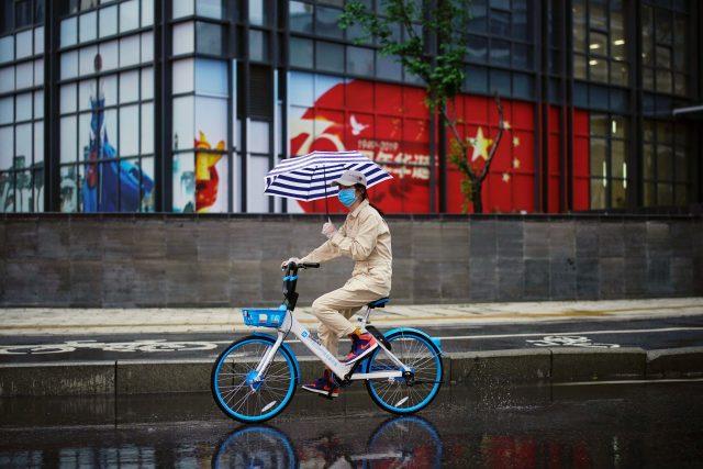Žena projíždí na sdíleném kole kolem čínské vlajky