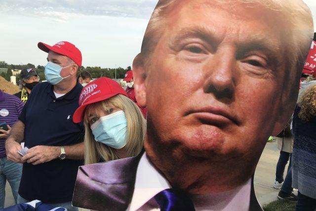 """Ptám se Trumpovy fanynky Dorly třímající prezidentovu podobiznu, jestli neměl být obecně zodpovědnější a dodržovat nařízení úřadů své vlastní vlády: """"Kdo ví, jak se to dá chytit… Přenáší se to vzduchem? Potřebujete roušku? Nepotřebujete roušku? Tolik nezn"""