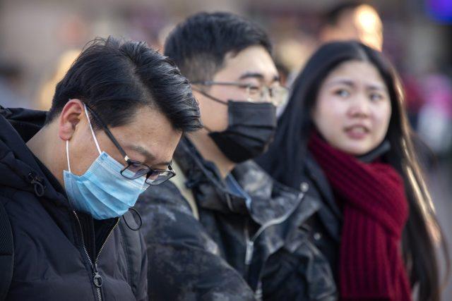 Cestující s rouškami před nádražím v Pekingu (fotografie z 20. ledna 2020)