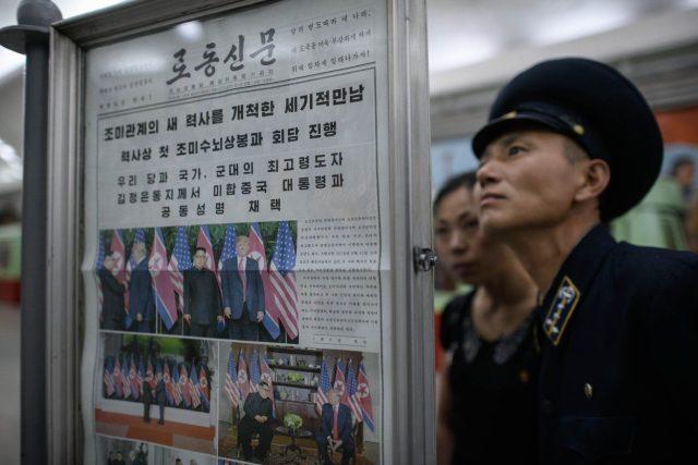 Průvodčí pchjongjangského metra jako jeden z obyvatel hlavního města KLDR,  kteří si ve vestibulu metra pročítají stránky státních novin Rodong Sinmun. Donald Trump přijal Kim Čong-unovo pozvání k návštěvě Pchjongjangu,  píše list ve svém vydání ze 13. 6. | foto: Kyodo, Profimedia