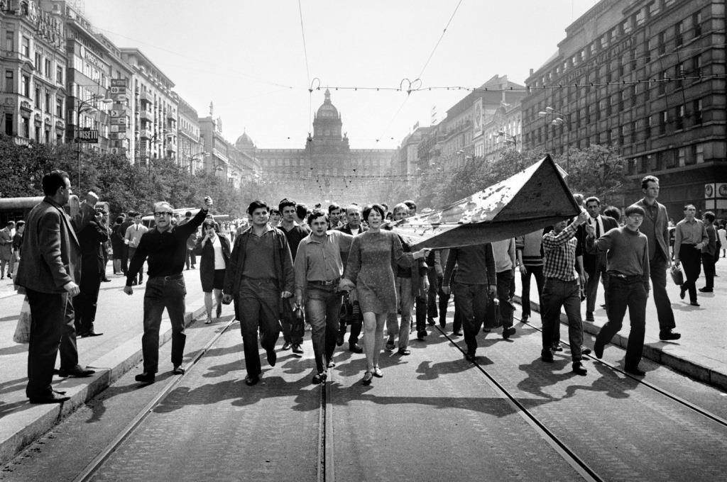 Lidé na Václavském náměstí nesou 21. srpna 1968 zkrvavenou státní vlajku