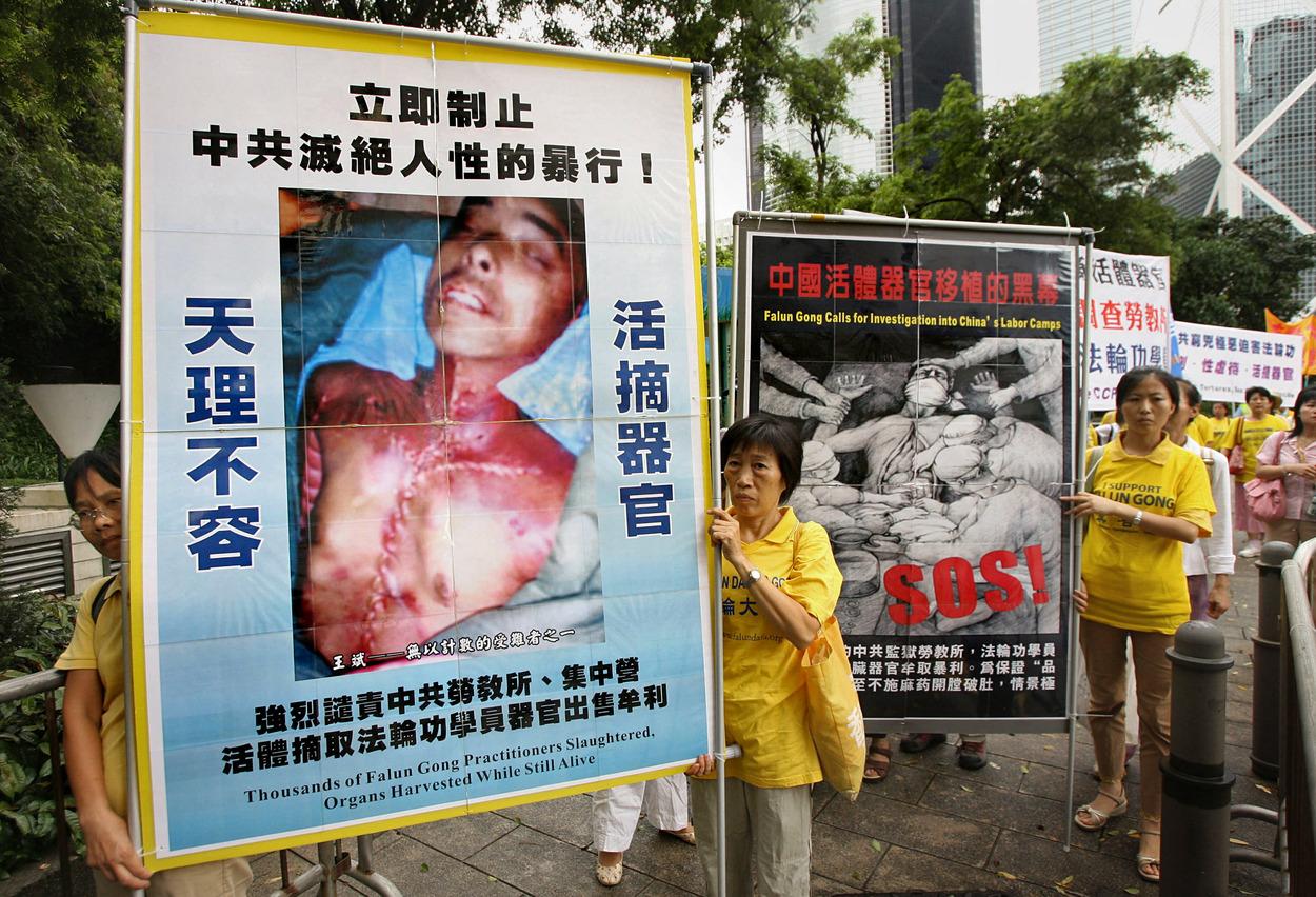Praktikující Fa-lun-kung protestují proti masovému odebírání orgánů vězňům v pevninské Číně, Hongkong, červen 2006.