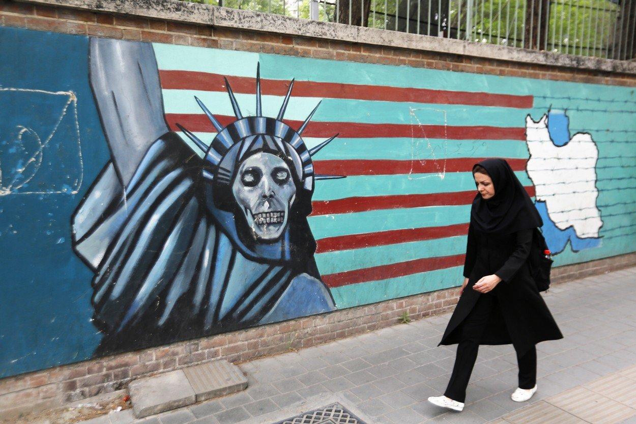 Íránka kráčí podél výmluvné nástěnné malby na zdi, která obklopuje areál bývalé americké ambasády v Teheránu (8. května 2018).